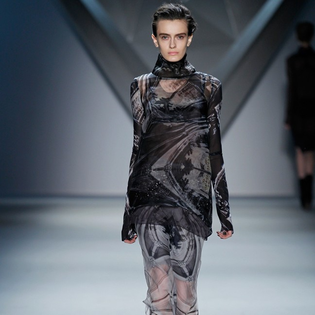 Look 32 | Black vault print silk organza long sleeve high neck top over plum organza racerback tank and black vault print silk chiffon bra over grey vault print silk chiffon floor-length skirt with crystal mesh zip-front peplum over grey ribbed knit bermuda short
