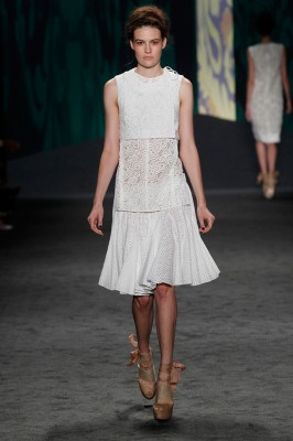Look 9: White lace jacquard cropped sleeveless choli jacket over white guipure tank with side vents over white cotton eyelet parasol skirt | Photography: Dan Lecca